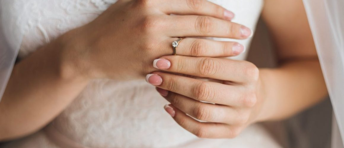 hands-bride-with-tender-french-manicure-precious-engagement-ring-with-shiny-diamond-wedding-dress-min