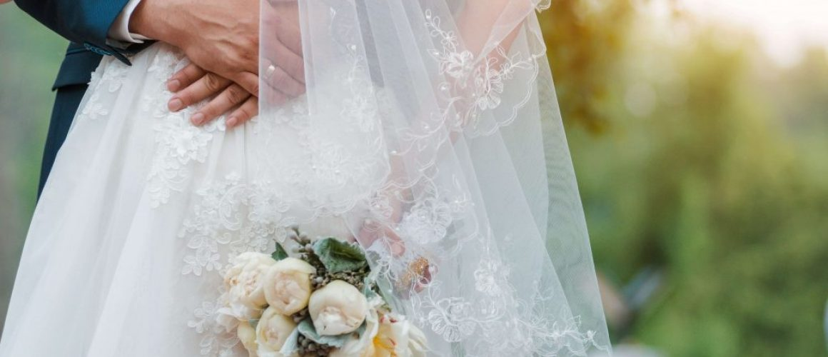 newly-married-couple-wedding-day-bouquet-bride-hands-groom-s-embrace-min (1)